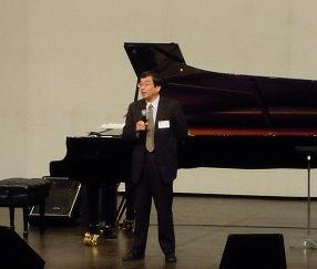 ステージで挨拶する事務局長の菅川